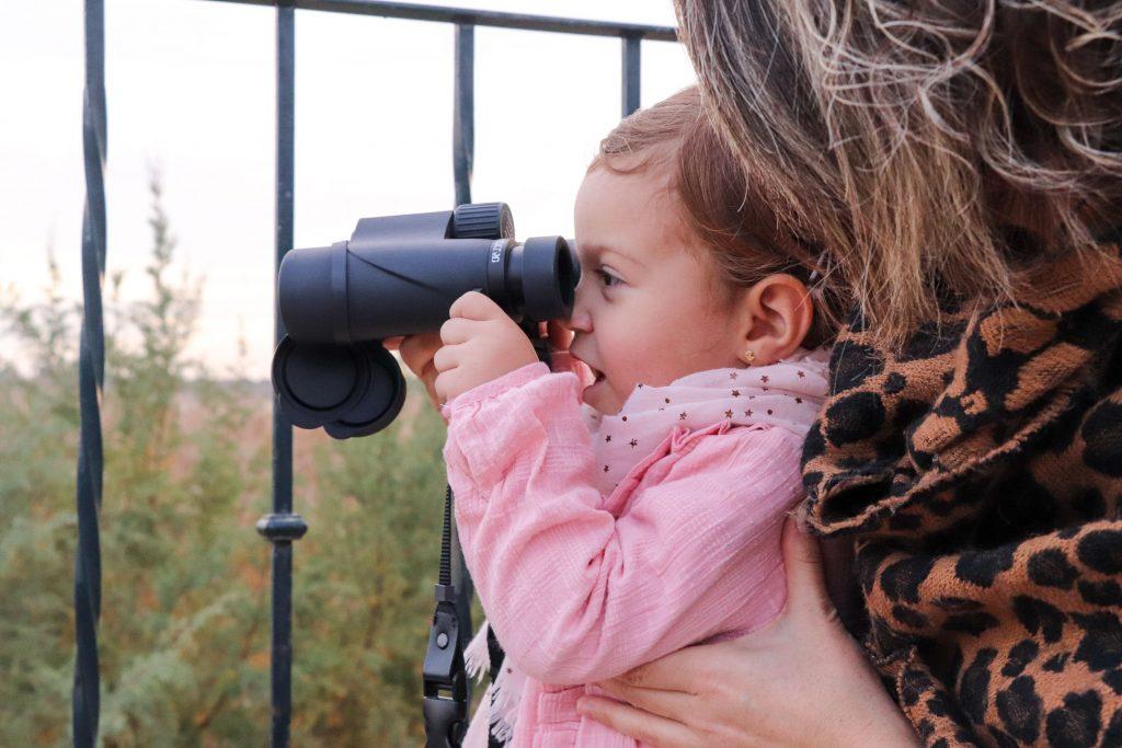 Niña observando aves a través de unos prismáticos
